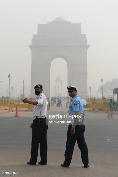 An Indian traffic policeman wearing a protection mask as he works near India Gate amid heavy smog in New Delh on November 13 2017 Schools reopened in...