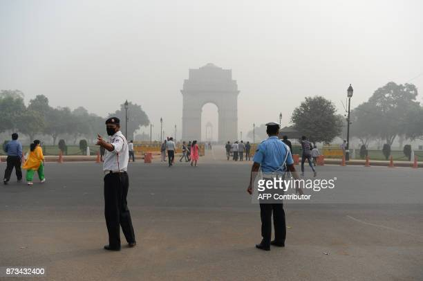 An Indian traffic policeman wearing a protection mask works near India Gate amid heavy smog in New Delh on November 13 2017 Schools reopened in New...