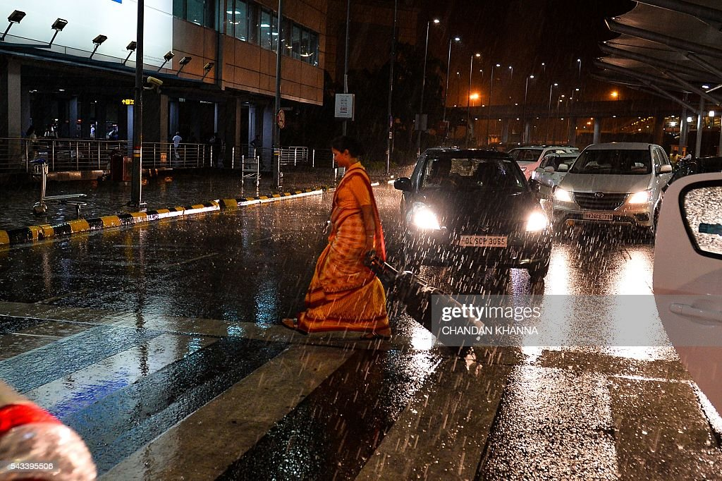 An Indian traveller crosses a road at the Delhi International Airport during heavy rain in New Delhi on early June 28, 2016. / AFP / CHANDAN
