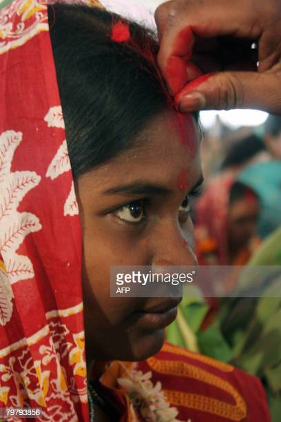 An Indian tribal bride is anointed by her groom as they take part in a mass marriage ceremony during a religious conference in Siliguri on February...
