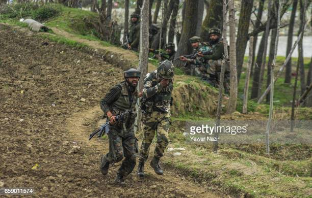 An Indian trooper rushes with his injured comrade who was during a gun battle between Indian government forces and suspected rebels on March 28 2017...