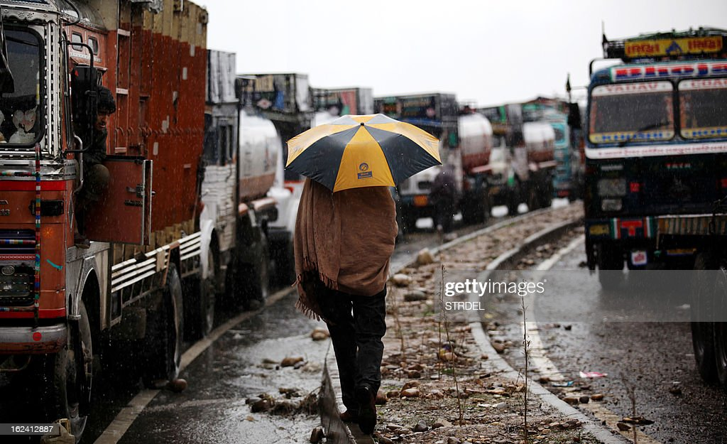An Indian truck driver walks near trucks stranded in heavy rain as they wait for the Jammu-Srinagar highway to reopen on the outskirts of Jammu on February 23, 2013. The Jammu-Srinagar National Highway remained closed for the second day even as fresh snowfall across Kashmir prompted authorities to issue an avalanche warning in higher reaches of the valley. AFP PHOTO/ STR