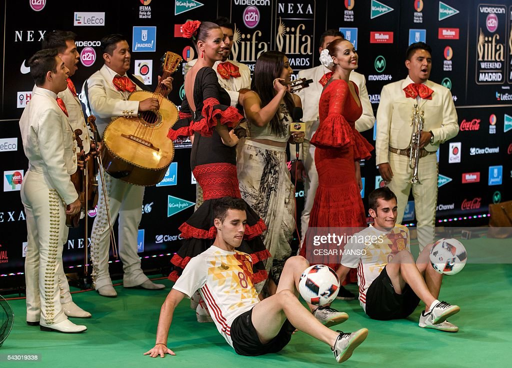 An Indian TV anchor (C) poses with Mariachis, footballers and dancers wearing Spanish Andalusian dresses on the green carpet few moments before the 17th edition of IIFA Awards (International Indian Film Academy Awards) in Madrid on June 25, 2016. The IIFA Awards are presented annually by the International Indian Film Academy to honour both artistic and technical excellence of professionals in Bollywood, the Hindi language film industry. / AFP / CESAR