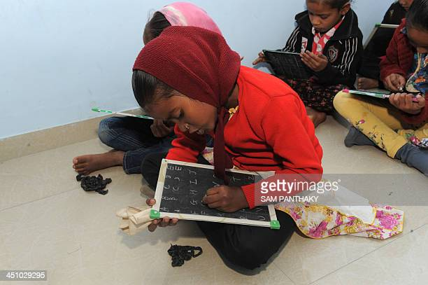 An Indian underprivileged child writes during lessons at Palodia village of Gandhinagar district some 25 kms from Ahmedabad on November 21 2013 Some...