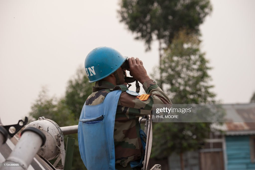 An Indian United Nations peacekeeper looks through binoculars towards M23 positions in Kanyarucinya on the outskirts of Goma in the east of the Democratic Republic of the Congo on July 14, 2013. Exchanges of artillery and rocket-fire broke out today between the Congolese army and M23 rebels, with impact visible from Kanyarucinya in the foot-hills of the Nyiragonga volcano.