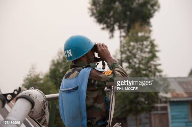 An Indian United Nations peacekeeper looks through binoculars towards M23 positions in Kanyarucinya on the outskirts of Goma in the east of the...
