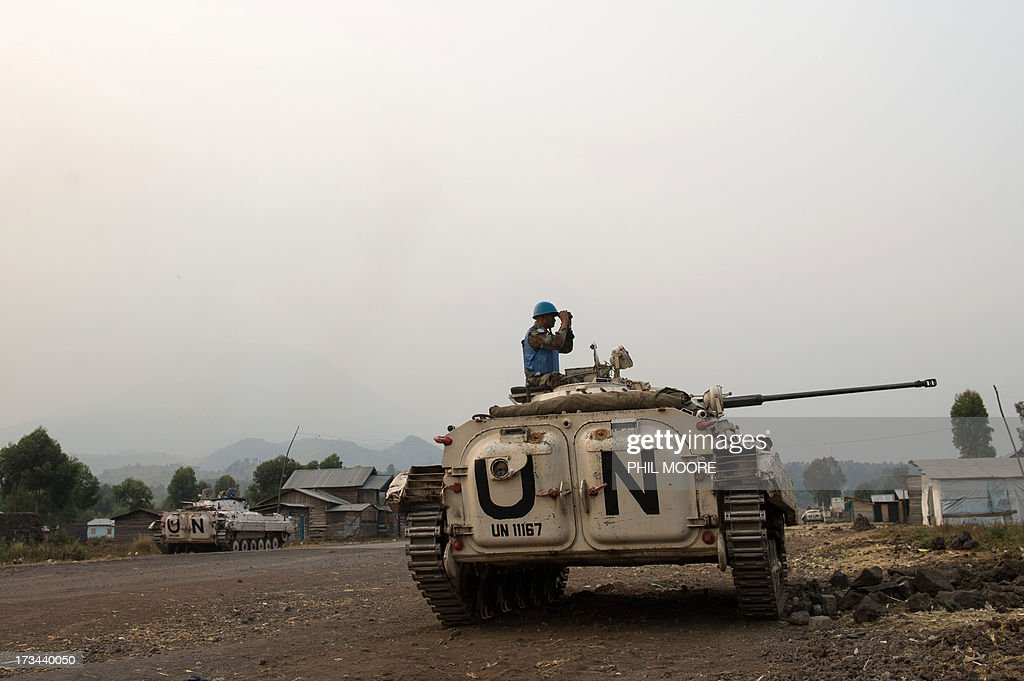 An Indian United Nations peacekeeper looks through binoculars towards M23 positions in Kanyarucinya on the outskirts of Goma in the east of the Democratic Republic of the Congo on July 14, 2013. Exchanges of artillery and rocket-fire broke out today between the Congolese army and M23 rebels, with impact visible from Kanyarucinya in the foot-hills of the Nyiragonga volcano. More than 55,000 refugees from eastern Democratic Republic of Congo have arrived in Uganda after fleeing a rebel attack, Red Cross officials said on July 14, although the rate of new arrivals has begun to slow down.