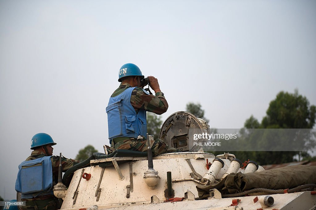 An Indian United Nations peacekeeper looks through binoculars towards M23 positions in Kanyarucinya on the outskirts of Goma in the east of the Democratic Republic of the Congo on July 14, 2013. Exchanges of artillery and rocket-fire broke out today between the Congolese army and M23 rebels, with impact visible from Kanyarucinya in the foot-hills of the Nyiragonga volcano. More than 55,000 refugees from eastern Democratic Republic of Congo have arrived in Uganda after fleeing a rebel attack, Red Cross officials said July 14, although the rate of new arrivals has begun to slow down. AFP PHOTO / PHIL MOORE