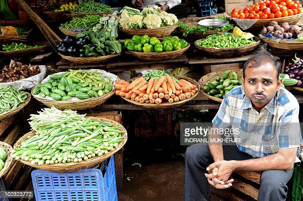An Indian vegetable seller waits for customers at a street side market in Mumbai on June 14 2010 Indian inflation broke into double figures in May...