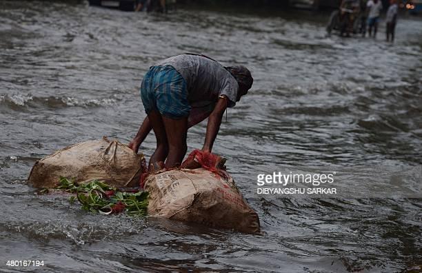 An Indian vegetable vendor floats sacks of produce along a waterlogged street following heavy rain in Kolkata on July 10 2015 AFP PHOTO/ Dibyangshu...