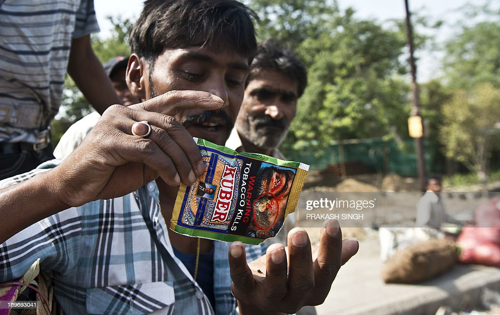 An Indian vegetable vendor prepares to eat chewing tobacco at a wholesale vegetable market in New Delhi on May 31, 2013. Observed around the world every year on May 31, World No Tobacco Day created by the World Health Organisation (WHO) this year has the theme 'Ban Tobacco Advertising, Promotion and Sponsorship'. AFP PHOTO/ Prakash SINGH