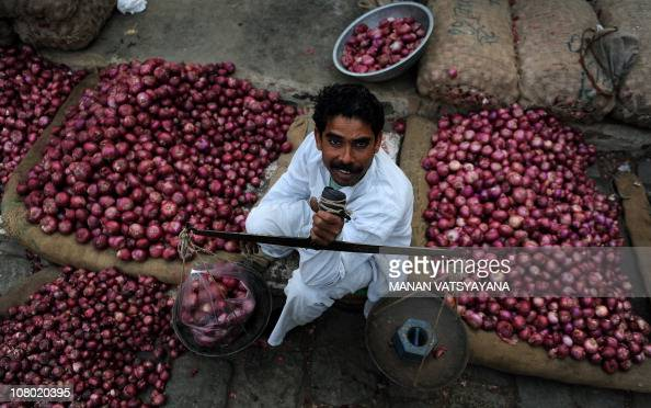 An Indian vegetable vendor weighs onions for customers at a wholesale market in New Delhi on February 17 2010 India's inflation has jumped to its...