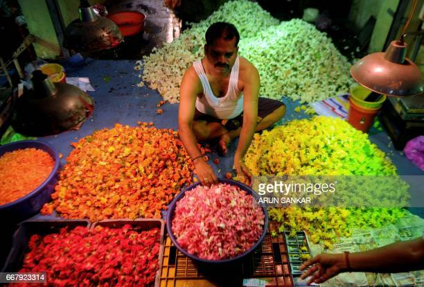 An Indian vendor arranges flowers on a stall at a flower market in Chennai on April 13 ahead of 'Vishu' or the New Year in accordance with the...