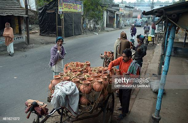 An Indian vendor arranges mudpots filled with jaggery cane sugar made from the date palm tree for sale at the market in Joynagar around 50 kms south...
