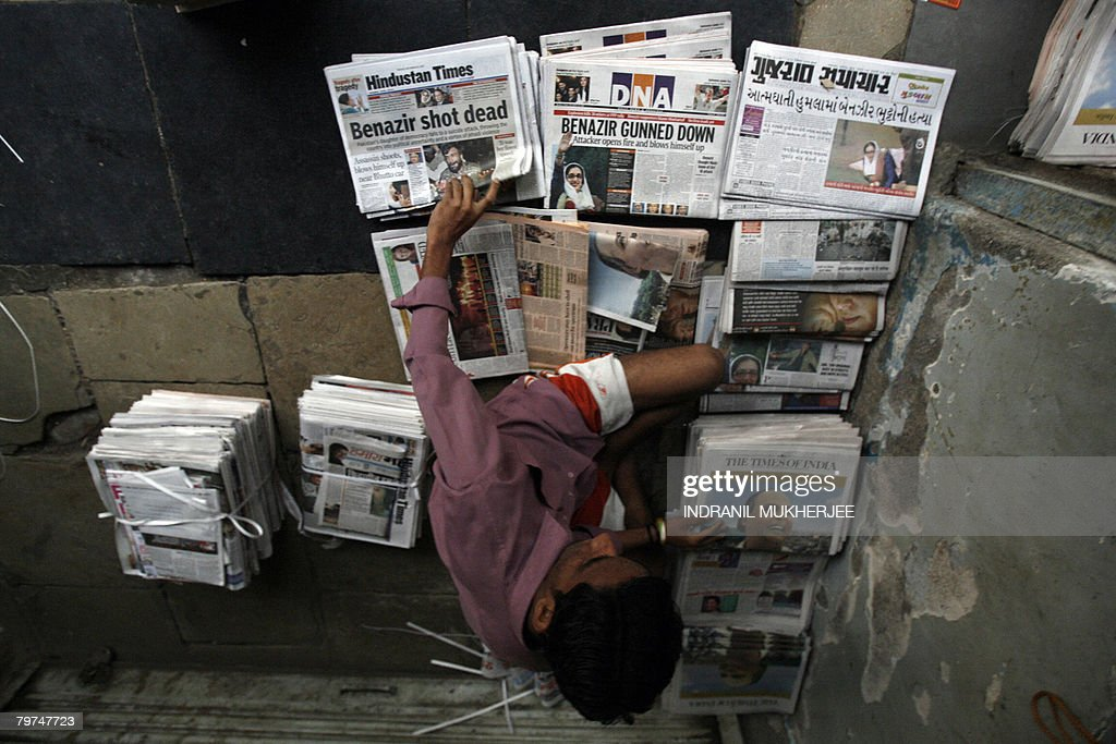 An Indian vendor arranges newspapers in Mumbai early 28 December 2007, with the reports of the assassination of former Pakistani premier Benazir Bhutto. Bhutto was assassinated by a suicide bomber, plunging the nation into one of the worst crises in its history and raising alarm around the world. Violence erupted in cities across Pakistan as mobs went on the rampage in a wave of anger that left at least 10 people dead and dozens wounded, officials said. AFP PHOTO/Indranil MUKHERJEE