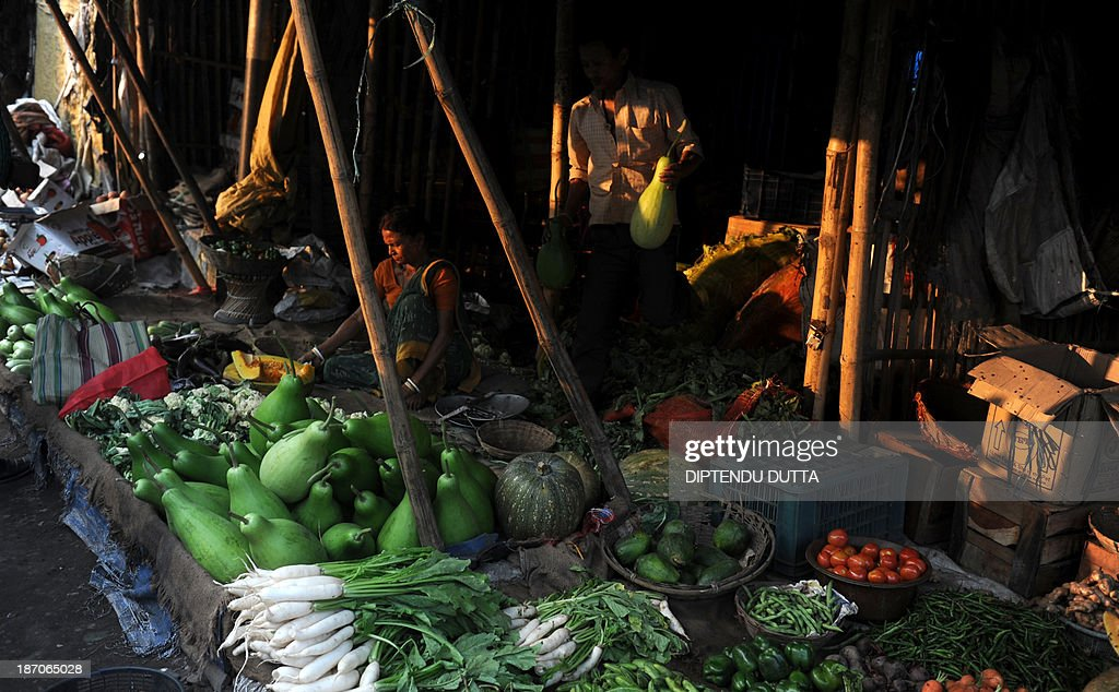 An Indian vendor arranges vegetables at a roadside market in Siliguri on November 6, 2013. The price of onions, a staple in Indian cooking have gone through the roof in the past few months, quadrupling to as much as 100 rupees a kilogram (1.65 dollar) in parts of the country and turning the vegetable into an unaffordable luxury for the poor. AFP PHOTO/Diptendu DUTTA