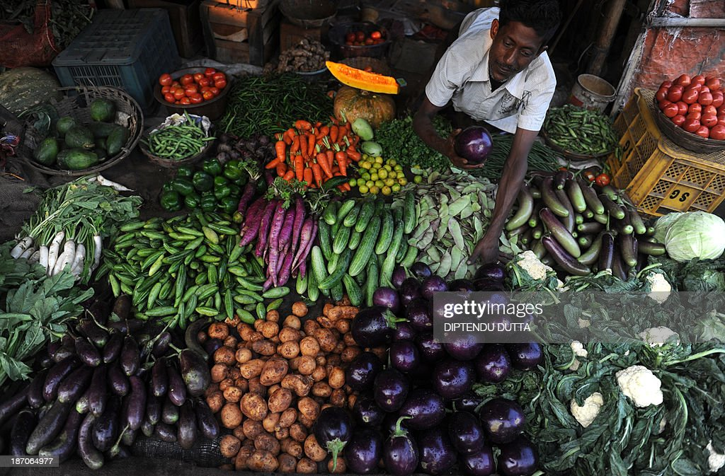 An Indian vendor arranges vegetables for sale at a roadside market in Siliguri on November 6, 2013. The price of onions, a staple in Indian cooking have gone through the roof in the past few months, quadrupling to as much as 100 rupees a kilogram (1.65 dollar) in parts of the country and turning the vegetable into an unaffordable luxury for the poor. AFP PHOTO/Diptendu DUTTA