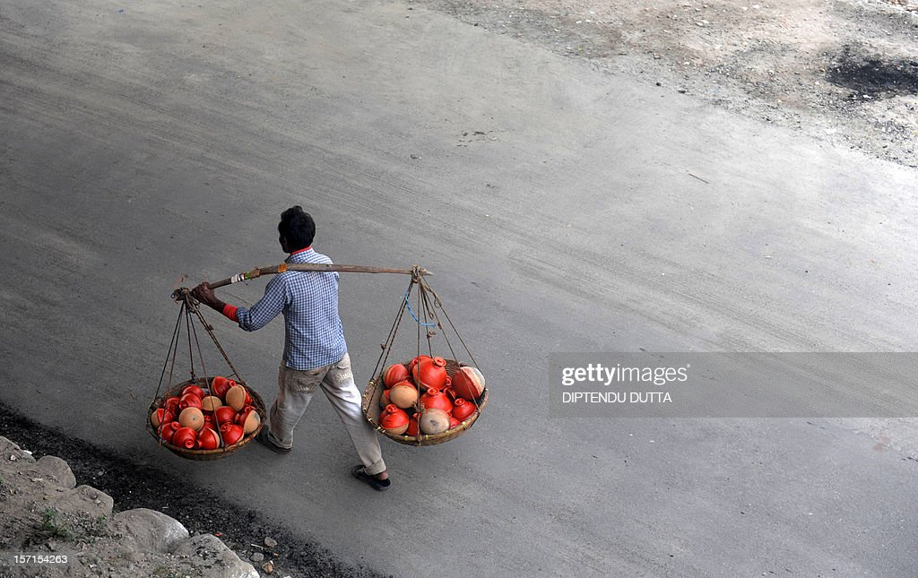 An Indian vendor carries earthen pots for sale in Siliguri on November 29, 2012. India's gross domestic product expanded at its slowest pace in three years in the second financial quarter, at 5.5 percent, down from near double-digit rates through much of 2005 to 2011. AFP PHOTO/ Diptendu DUTTA