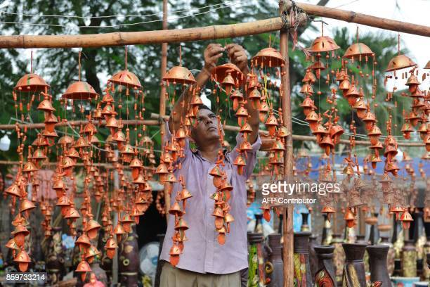 An Indian vendor display chimes in the shape of bells on sale at a roadside stall ahead of the Diwali festival in Amritsar on October 10 2017 / AFP...