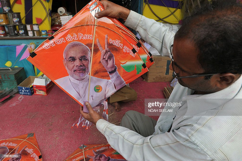 An Indian vendor displays a kite printed with the portrait of Gujarat state Chief Minister Narendra Modi ahead of the forthcoming Makar Sankranti kite festival in Hyderabad on January 9, 2013. The Makar Sankranti festival, which will be celebrated on January 14 this year, celebrates the beginning of the harvest season. AFP PHOTO/Noah SEELAM