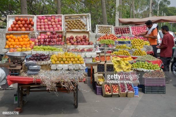 An Indian vendor displays fruit for sale at a roadside stall in Amritsar on June 16 2017 / AFP PHOTO / NARINDER NANU