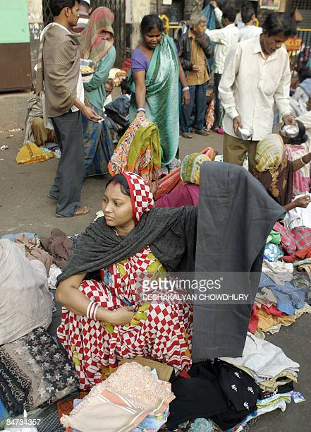An Indian vendor displays her wares as bargain hunters browse through clothing at a second hand clothing market in Kolkata on February 11 2009 The...