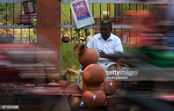 An Indian vendor fixes a tap to an earthern pot at his shop on the pavement next to a road in Chennai on April 21 2017 / AFP PHOTO / ARUN SANKAR