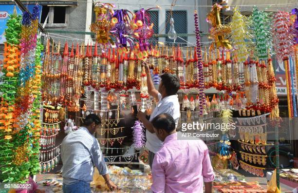 An Indian vendor hangs decorative items to sell ahead of Diwali festival at a roadside stall in Amritsar on October 16 2017 / AFP PHOTO / NARINDER...