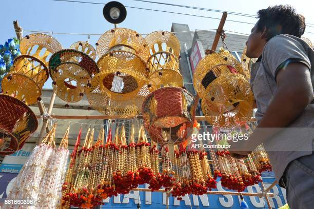 An Indian vendor hangs decorative lanterns to sell ahead of Diwali festival at a roadside stall in Amritsar on October 16 2017 / AFP PHOTO / NARINDER...