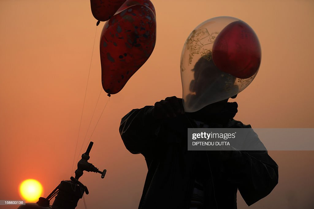 An Indian vendor inflates balloons as the sunsets in Siliguri on December 31, 2012. Sydney will kick off a wave of dazzling firework displays welcoming in 2013, from Dubai to Moscow and London, with long-isolated Yangon joining the global pyrotechnics for the first time. AFP PHOTO/Diptendu DUTTA