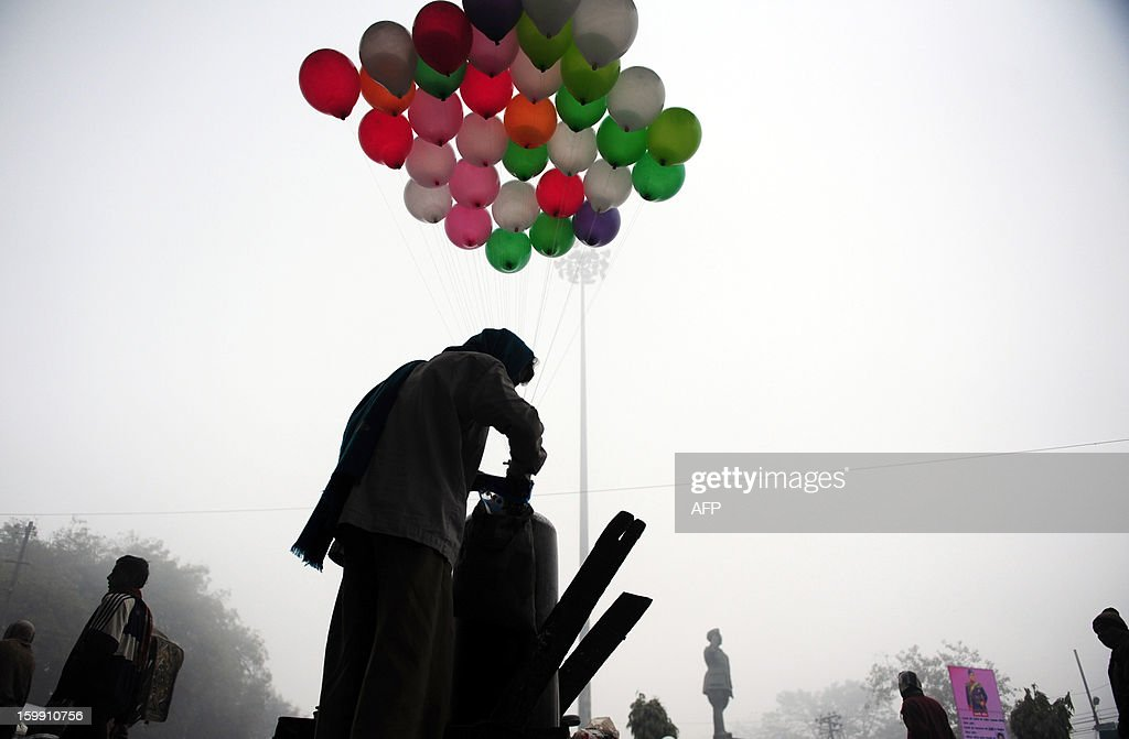 An Indian vendor inflates balloons during a foggy and cold morning in Allahabad on January 23, 2013.The once-booming Indian economy has been hit by continuing high interest rates in the face of strong inflation, sluggish exports and slow investment. AFP PHOTO/ Sanjay KANOJIA
