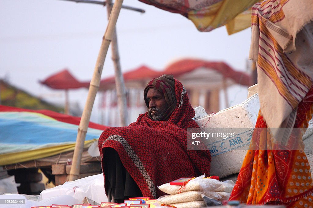 """An Indian vendor keeps warm on the banks of """"Sangam,"""" the confluence of the three rivers Ganges, Yamuna and mythical Saraswati in Allahabad on December 22, 2012, ahead of the Mahakumbh Mela. The Kumbh Mela, which is scheduled to take place in the northern Indian city in January and February 2013, is the world's largest gathering of people for a religious purpose and millions of people gather for this auspicious occasion. AFP PHOTO/ Sanjay KANOJIA"""