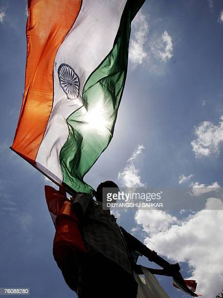 An Indian vendor looks on as he sells Indian national flags to motorists and commuters on a busy city street in Bangalore 14 August 2007 The whole...