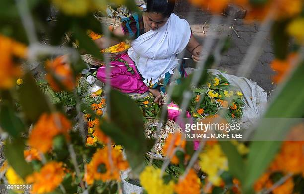 An Indian vendor makes a 'toran' a floral door hanging at her roadside stall on 'Gudi Padwa' or the Maharashtrian new year in Mumbai on April 11 2013...
