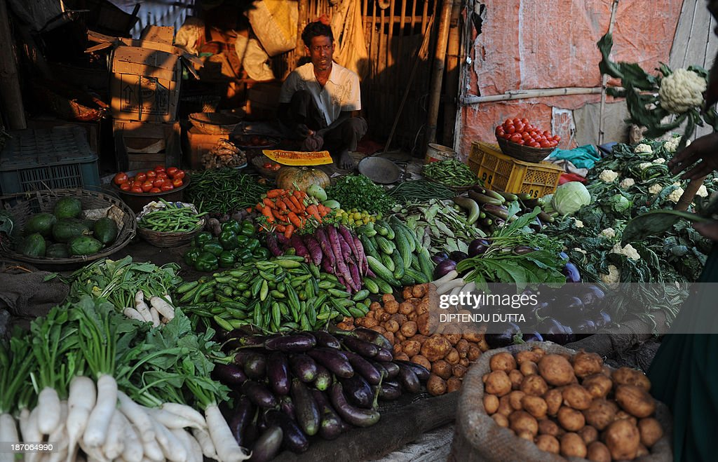 An Indian vendor negotiates with customers at a roadside vegetable market in Siliguri on November 6, 2013. The price of onions, a staple in Indian cooking have gone through the roof in the past few months, quadrupling to as much as 100 rupees a kilogram (1.65 dollar) in parts of the country and turning the vegetable into an unaffordable luxury for the poor. AFP PHOTO/Diptendu DUTTA