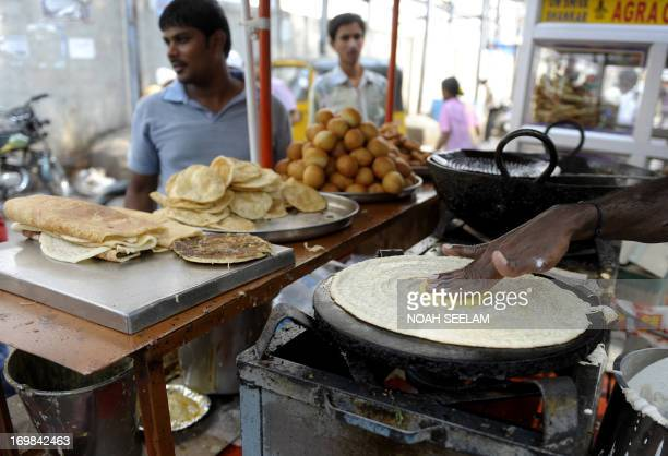 An Indian vendor prepares masala dosa at a roadside stall in Hyderabad on June 3 2013 The National Food Security Bill considered to be the world's...
