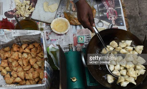 An Indian vendor prepares samosas at a roadside stall in New Delhi on January 14 2016 One of India's poorest states has said it will impose a 'luxury...