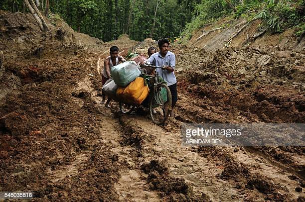 An Indian vendor pushes his bicycle laden with goods through heavy mud on National Highway 44 at Khasiapunji some 205 kms north of Agartala on the...
