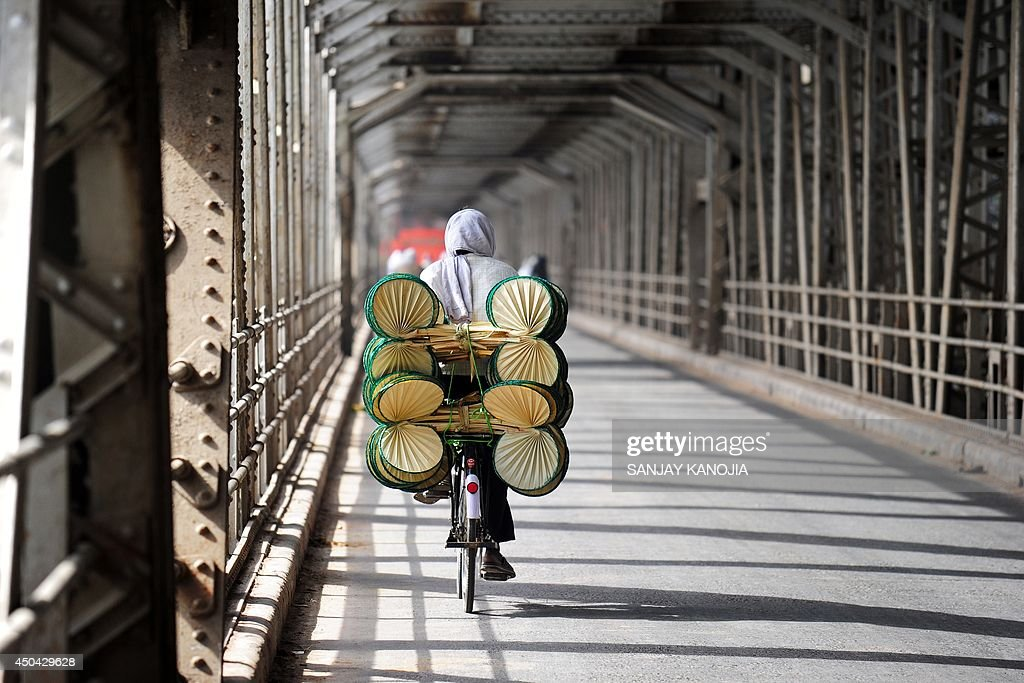 An Indian vendor selling hand fans cycles across the Yamuna bridge with his wares on a hot summer afternoon in Allahabad on June 11, 2014. Temperatures across many parts of northern India hovered around the mid-40 degrees Celsius mark, with the continued heatwave to last through the week, according to metereological officials.