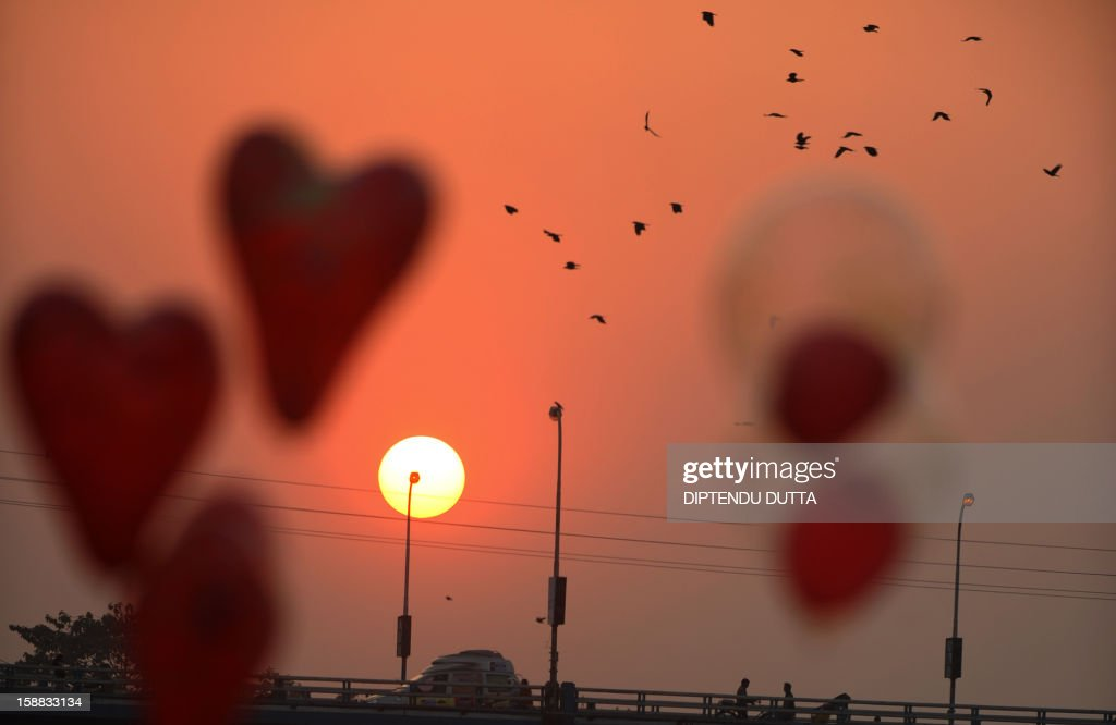 An Indian vendor sells balloons as the sunsets in Siliguri on December 31, 2012. Sydney will kick off a wave of dazzling firework displays welcoming in 2013, from Dubai to Moscow and London, with long-isolated Yangon joining the global pyrotechnics for the first time. AFP PHOTO/Diptendu DUTTA