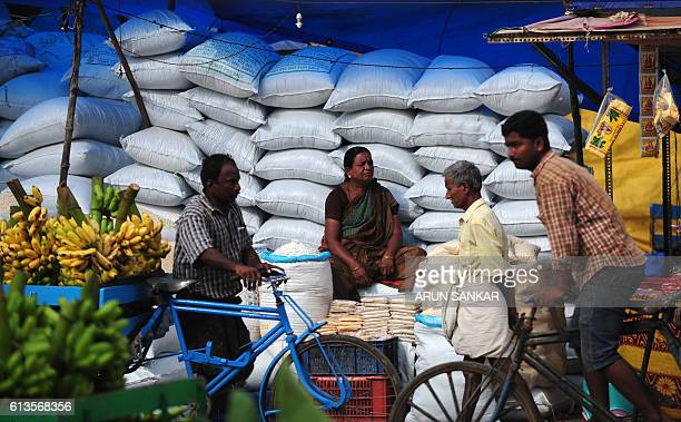 An Indian vendor sits among sacks of rice pops as she waits for customer at wholesale flower market in Chennai on October 9 2016 / AFP / ARUN SANKAR