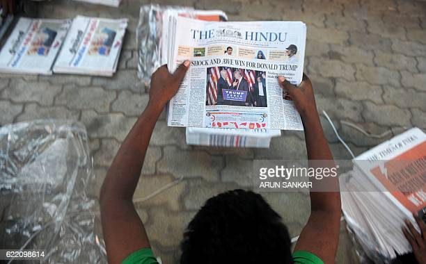 An Indian vendor sorts newspapers that show the headlines of US Presidentelect Donald Trump's victory on a street in Chennai on November 10 the day...