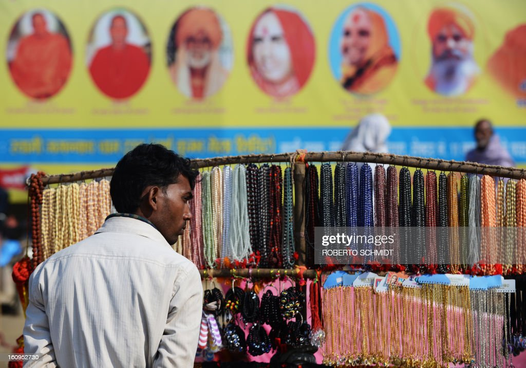 An Indian vendor stands near a bill board showing Hindu Gurus near a street in the sprawling grounds of the Maha Kumbh Mela festival in Allahabad on February 8, 2013. The Kumbh Mela in the town of Allahabad will see up to 100 million worshippers gather over 55 days to take a ritual bath in the holy waters, believed to cleanse sins and bestow blessings.
