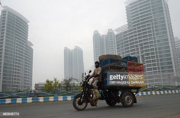 An Indian vendor transport chickens in crates as he drives past high rise buildings on a foggy morning in Kolkata on January 1 2015 Seasonal fog and...