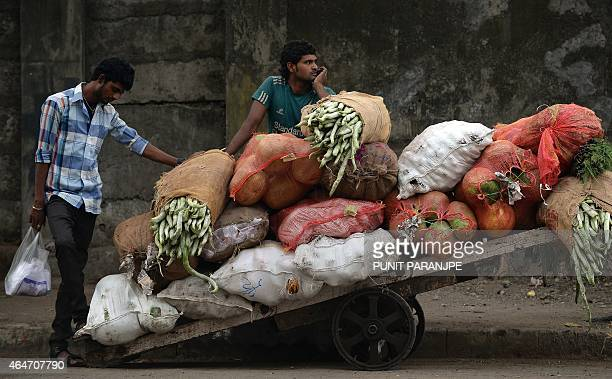 An Indian vendor waits alonside his cart filled with vegetables at the whole sale market in Mumbai on February 28 2015 Prime Minister Narendra Modi's...