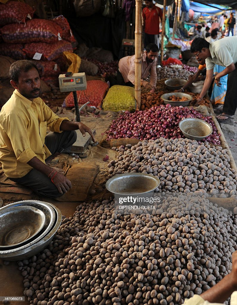An Indian vendor waits as customers select onions and potatoes at a roadside vegetable market in Siliguri on November 6, 2013. The price of onions, a staple in Indian cooking have gone through the roof in the past few months, quadrupling to as much as 100 rupees a kilogram (1.65 dollar) in parts of the country and turning the vegetable into an unaffordable luxury for the poor. AFP PHOTO/Diptendu DUTTA