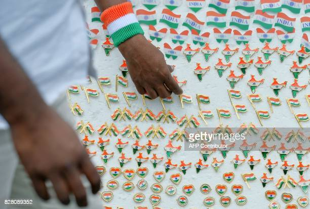 An Indian vendor waits for customers to sell pins depicting the national flag at a rally held to commemorate the 75th year of the Quit India freedom...