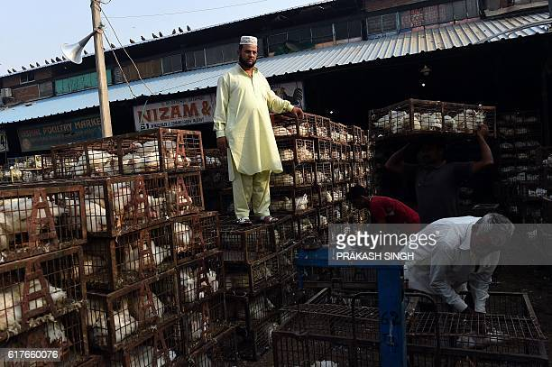 An Indian vendor waits for customers while standing on chicken cages outside his shop at a poultry market in New Delhi on October 24 2016 New Delhi...