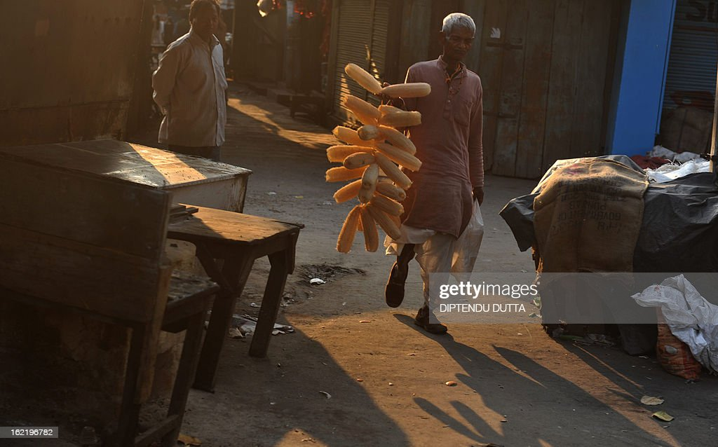 An Indian vendor walks past closed shops at a market during a two-day strike called by trade unions opposing the current UPA government's economic policies in Siliguri on February 20, 2013. Millions of India's workers walked off their jobs in a two-day nationwide strike called by trade unions to protest at the 'anti-labour' policies of the embattled government. Financial services and transport were hit by the strike called by 11 major workers' groups to protest at a series of pro-market economic reforms announced by the government last year, as well as high inflation and rising fuel prices.