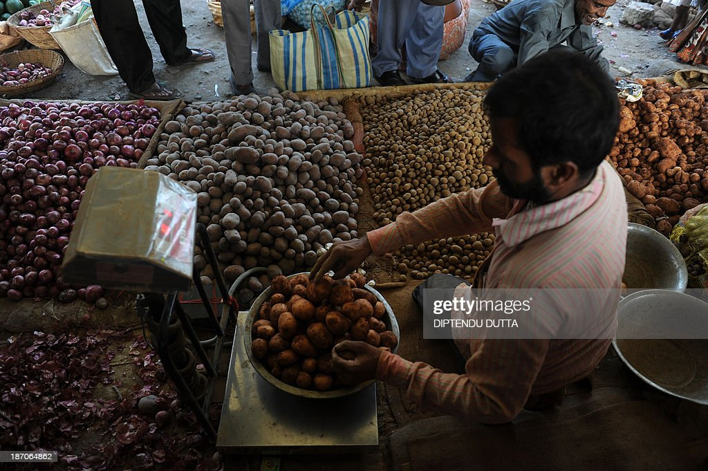 An Indian vendor weighs potatoes at a roadside vegetable market in Siliguri on November 6, 2013. The price of onions, a staple in Indian cooking have gone through the roof in the past few months, quadrupling to as much as 100 rupees a kilogram (1.65 dollar) in parts of the country and turning the vegetable into an unaffordable luxury for the poor. AFP PHOTO/Diptendu DUTTA